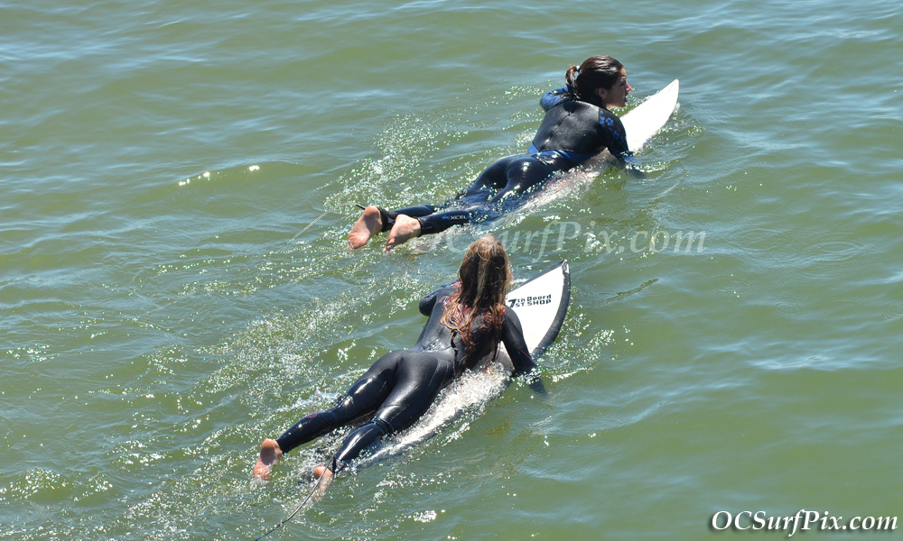 two female surfers heading out